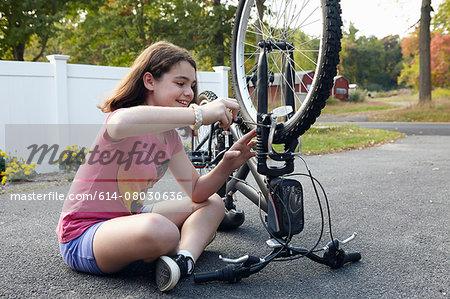 Girl repairing bicycle on driveway