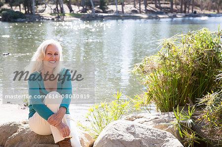 Senior woman by lake, Hahn Park, Los Angeles, California, USA