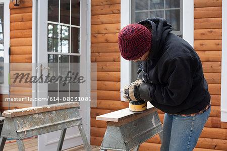 Mature woman sanding wooden plank outside house