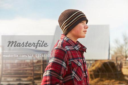 Portrait of boy wearing knit hat in dairy farm yard