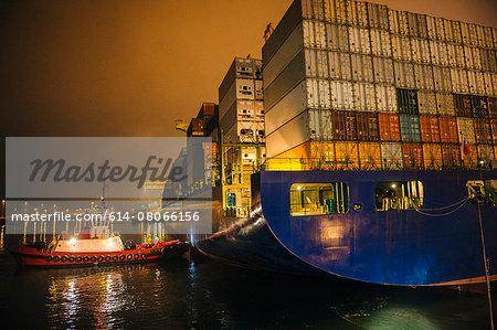 Tugboat manoeuvring container ship on river at night, Tacoma, Washington, USA