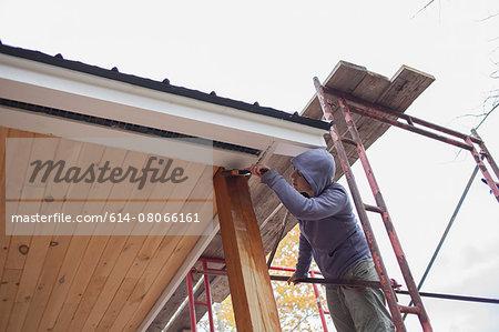 Mid adult woman painting varnish on wood outside house