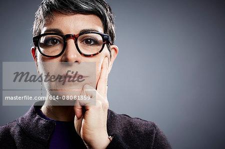 Studio portrait of mature businesswoman hand on cheek