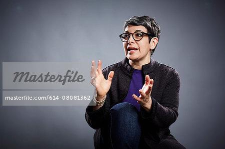 Studio portrait of mature businesswoman explaining with open hands