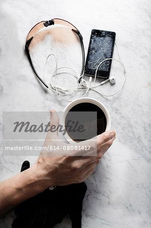 Hand of bike messenger with coffee, glasses, broken smartphone