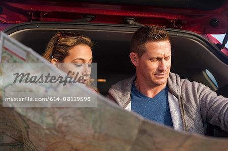 Couple reading map behind vehicle