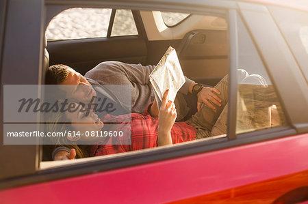 Couple reading map inside vehicle