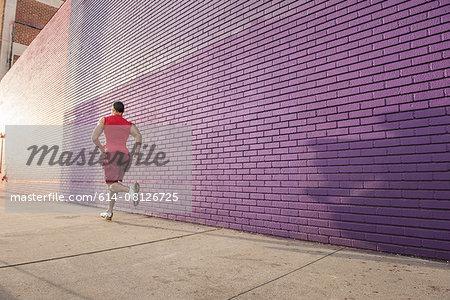 Rear view of male runner running along sidewalk