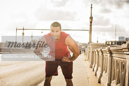 Male runner taking a break on bridge, Los Angeles, California, USA