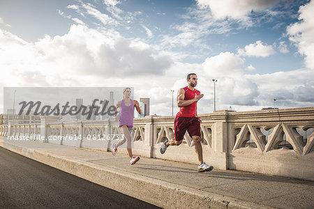Male and female runners running across bridge, Los Angeles, California, USA