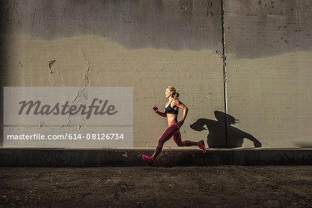 Female runner running on sidewalk