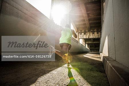 Male runner running under city bridge