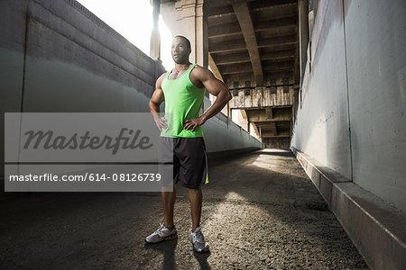 Male runner taking a break under city bridge