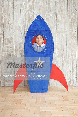 Girl looking up from window of blue homemade  cardboard rocket