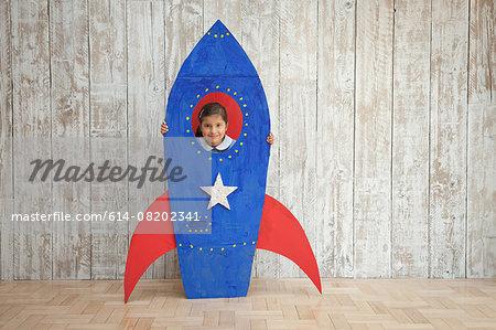 Portrait of girl looking from window of blue homemade  cardboard rocket