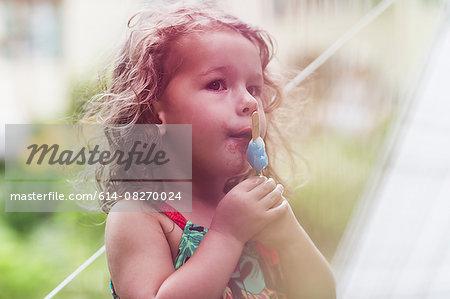 Girl eating melting ice lolly in garden