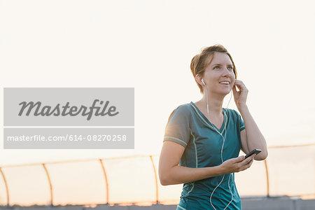 Mid adult woman, wearing earphones, outdoors