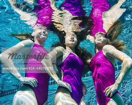 Three female swimmers, underwater, hands on hips
