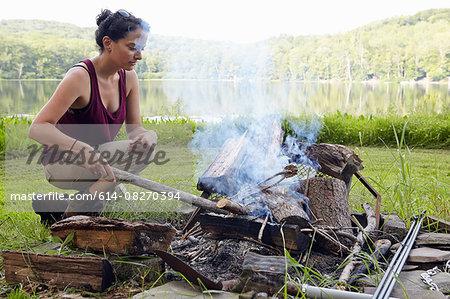 Female hiker making a campfire on lakeside, New Milford, Pennsylvania, USA
