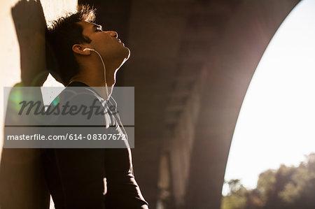 Jogger taking break under arch bridge, Arroyo Seco Park, Pasadena, California, USA