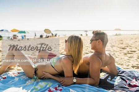 Young couple sunbathing on Newport Beach, California, USA