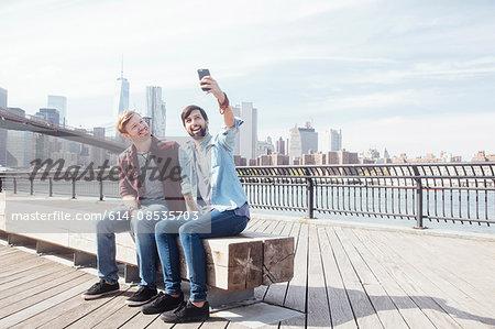 Male couple sitting on riverside by Brooklyn Bridge taking smartphone selfie, New York, USA