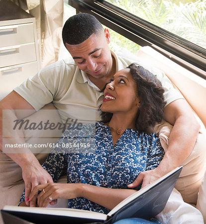 Couple reading book on sofa