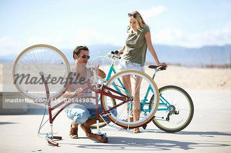 Couple repairing bicycle at Venice Beach, Los Angeles, California, USA