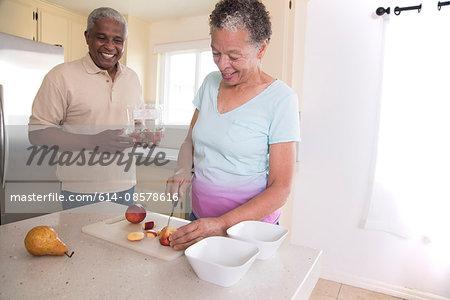 Senior couple in kitchen making fruit salad, woman chopping fruit