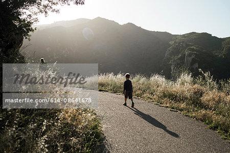 Boy walking along rural road, Santa Barbara, California, USA