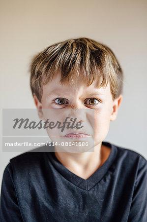 Studio portrait of boy pulling wrinkled face