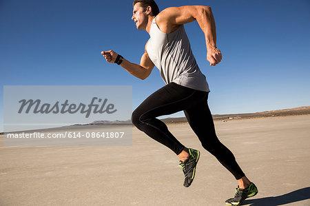 Man training, running on dry lake bed, El Mirage, California, USA