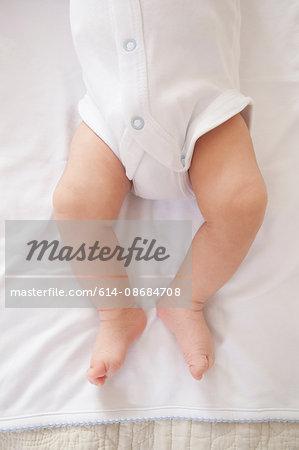 Waist down of baby boy wearing romper suit