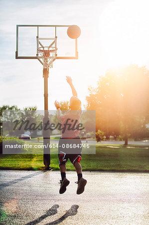 Young boy shooting basketball jump shot