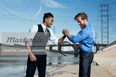 Businessmen arm wrestling, Los Angeles river, California, USA