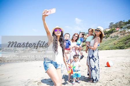 Mother taking selfie of friends and babies on beach, Malibu, California, USA