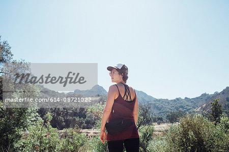 Rear view of woman in the mountains looking away, Malibu, California, USA
