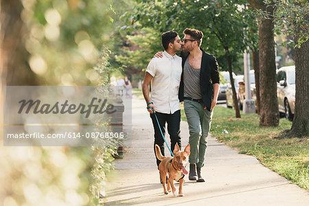 Young male couple kissing, walking dog on suburban sidewalk