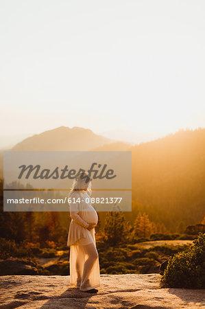 Pregnant woman in mountains touching stomach, Sequoia national park, California, USA