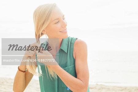 Woman on beach plaiting hair