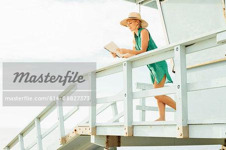 Woman on lifeguard tower reading magazine