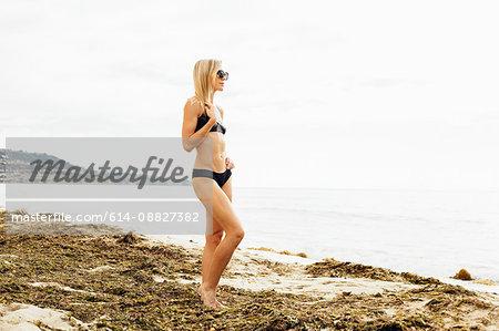 Woman wearing bikini on beach looking away