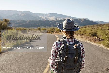 Woman standing in desert road, looking ahead, Sedona, Arizona, USA