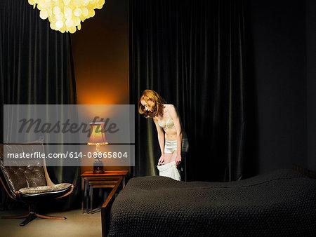 Woman in underwear standing in bedroom