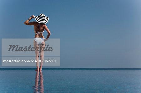 Woman in bikini at edge of infinity pool