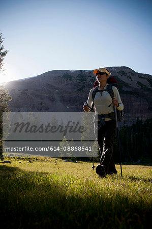 Hiker carrying pack on grassy hillside