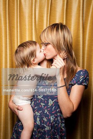 Woman kissing baby daughter