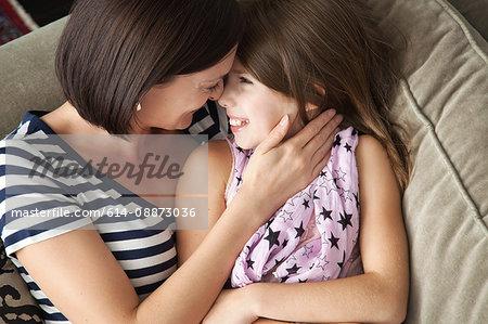 Mid adult woman hugging daughter on sofa