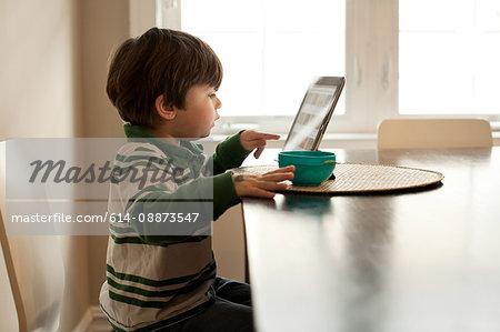 Boy using digital tablet at table