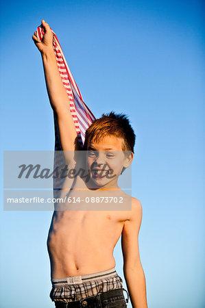 Boy holding striped fabric, arm raised